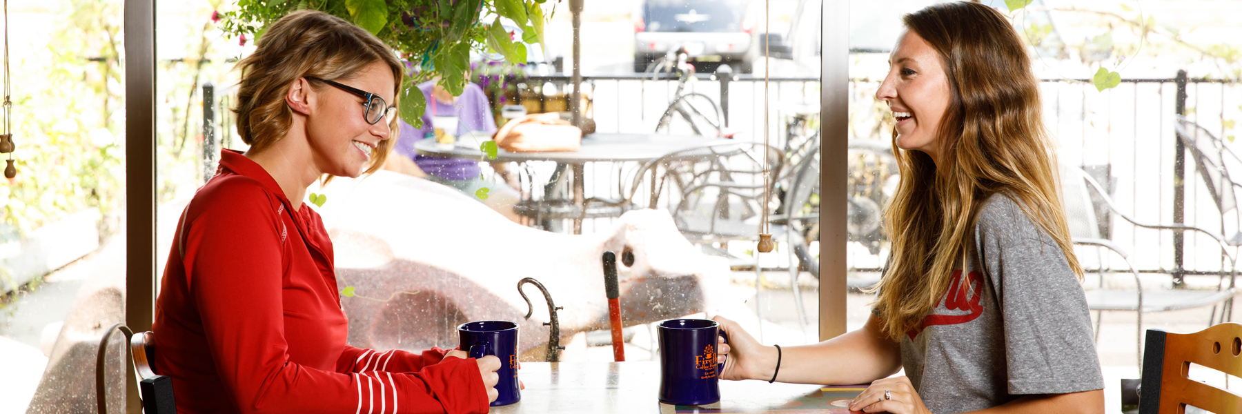 Two students smile and talk over mugs of coffee in a coffee shop.