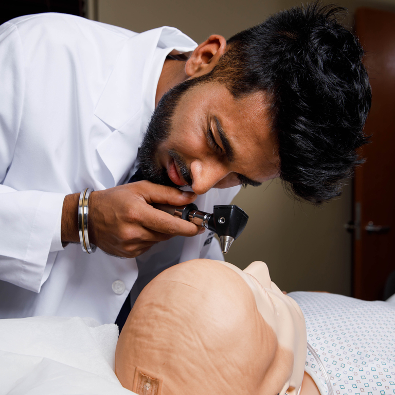 A medical student examines the eye of a teaching mannequin.