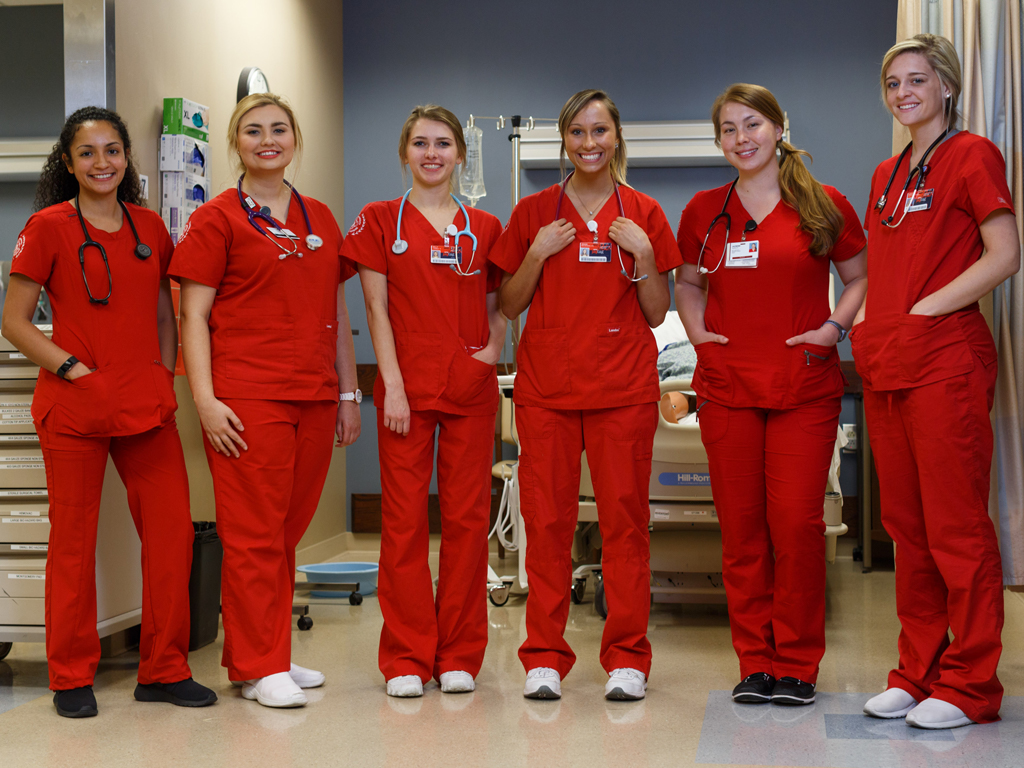 Six nursing students in red scrubs smile for the camera.