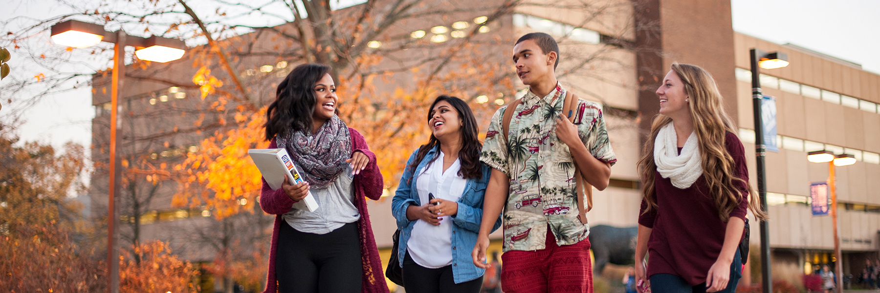 A group of students chat as they walk on campus during the fall.