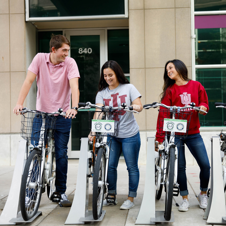 Three students take advantage of Fort Wayne's bike share program.