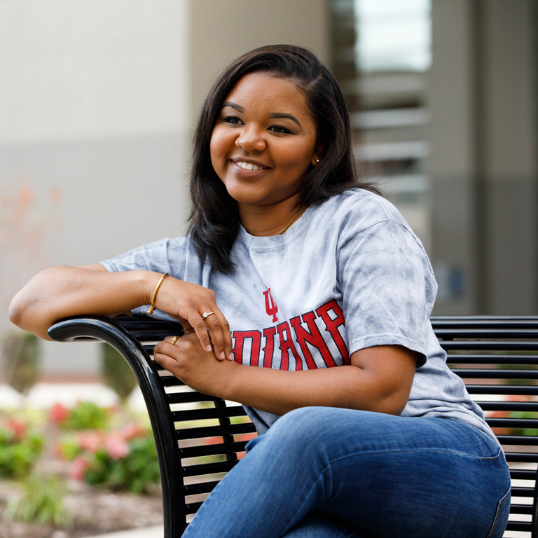 A student wearing an Indiana University T-shirt sits on a bench outside.