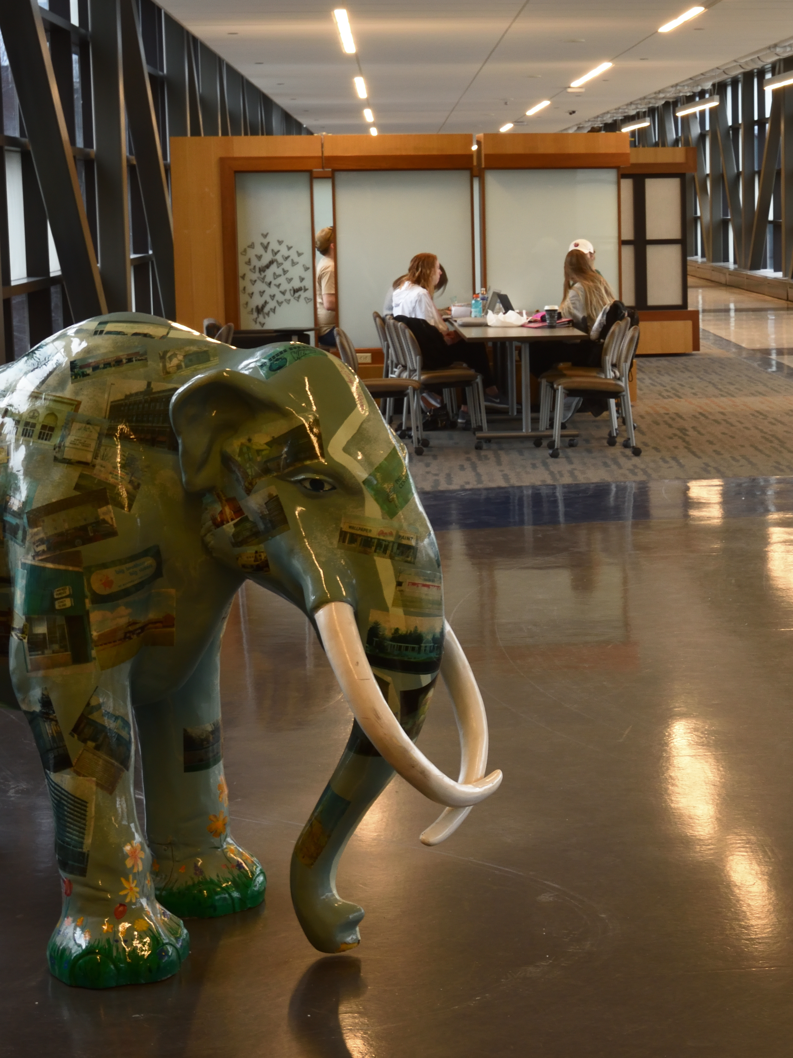 Study group in background with brightly painted mastodon in foreground.